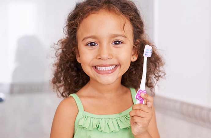 Girl Smiling holding tooth brush